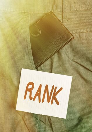 Word writing text Rank. Business photo showcasing The showing or things that belong to a particular organization or group Small little wallet inside man trousers front pocket near notation paper Standard-Bild