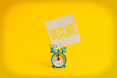 Word writing text Decline. Business photo showcasing Become smaller fewer less Decrease Politely refuse reject say no Metal retro vintage alarm clock blank sticky note sheet colored background
