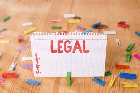 Conceptual hand writing showing Legal. Concept meaning Allowable or enforceable by being in conformity with the law Colored crumpled papers wooden floor background clothespin