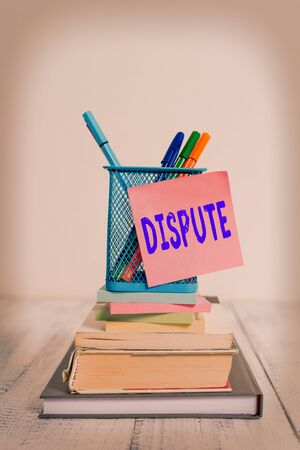 Handwriting text Dispute. Conceptual photo the serious argument or disagreement between showing or groups Stacked books pens metal holder sticky note lying vintage old wooden table Archivio Fotografico