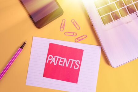 Handwriting text writing Patents. Conceptual photo government authority or licence conferring a right or title Trendy laptop smartphone marker paper sheet note clips colored background