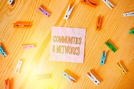 Word writing text Communities And Networks. Business photo showcasing Collaboration of Learnings and Practices of Members Colored clothespin papers empty reminder wooden floor background office