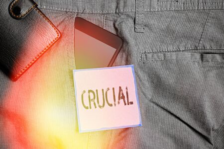 Conceptual hand writing showing Crucial. Concept meaning critical especially in the success or failure of something Smartphone device inside trousers front pocket with wallet