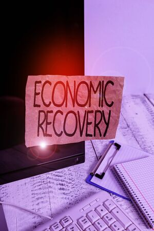 Conceptual hand writing showing Economic Recovery. Concept meaning rise of business activity signaling the end of a recession Note paper taped to black screen near keyboard stationary