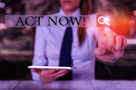 Text sign showing Act Now. Business photo showcasing do not hesitate and start working or doing stuff right away Female business person sitting by table holding mobile phone