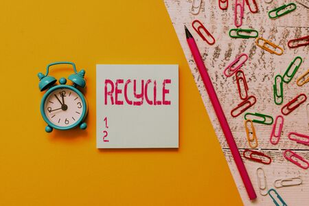 Word writing text Recycle. Business photo showcasing ocess of converting waste materials into new materials and objects Notepad marker pen colored paper sheet clips alarm clock wooden background
