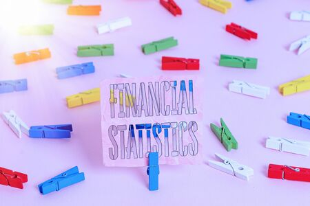 Handwriting text Financial Statistics. Conceptual photo Comprehensive Set of Stock and Flow Data of a company Colored clothespin papers empty reminder pink floor background office pin