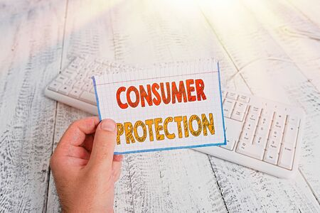 Text sign showing Consumer Protection. Business photo text Fair Trade Laws to ensure Consumers Rights Protection man holding colorful reminder square shaped paper white keyboard wood floor Banque d'images