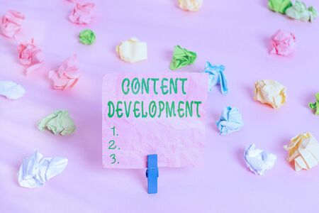 Handwriting text Content Development. Conceptual photo Specialized in Graphic Design Multimedia Documentation Colored crumpled papers empty reminder pink floor background clothespin