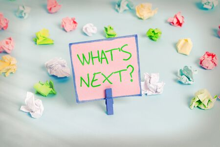Text sign showing What S Next Question. Business photo text Get information Ask Query Investigate Probes Explore Colored crumpled papers empty reminder blue floor background clothespin