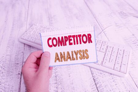 Text sign showing Competitor Analysis. Business photo text Determine the Strength Weakness of Competitive Market man holding colorful reminder square shaped paper white keyboard wood floor Foto de archivo