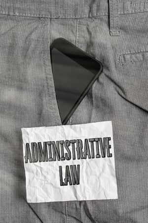 Text sign showing Administrative Law. Business photo text Body of Rules regulations Orders created by a government Smartphone device inside formal work trousers front pocket near note paper