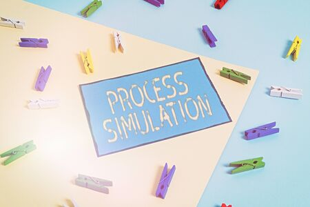 Text sign showing Process Simulation. Business photo showcasing Technical Representation Fabricated Study of a system Colored clothespin paper empty reminder yellow blue floor background office
