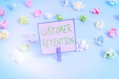 Text sign showing Customer Retention. Business photo text Keeping loyal customers Retain many as possible Colored crumpled papers empty reminder blue floor background clothespin Stockfoto