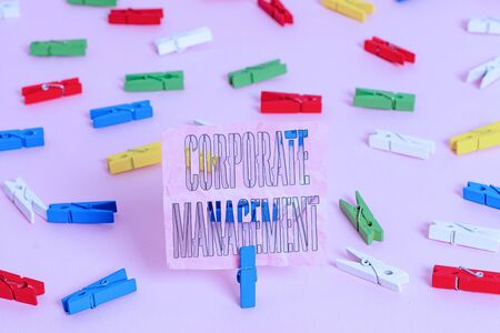 Handwriting text Corporate Management. Conceptual photo all Levels of Managerial Personnel and Excutives Colored clothespin papers empty reminder pink floor background office pin Stockfoto