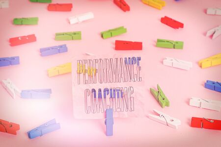 Handwriting text Performance Coaching. Conceptual photo Facilitate the Development Point out the Good and Bad Colored clothespin papers empty reminder pink floor background office pin