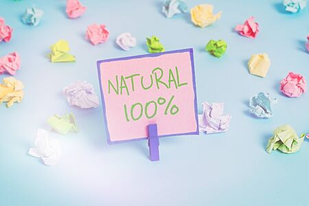 Text sign showing Natural 100 Percent. Business photo text Minimally processed and does not contain artificial flavors Colored crumpled papers empty reminder blue floor background clothespin Stock Photo