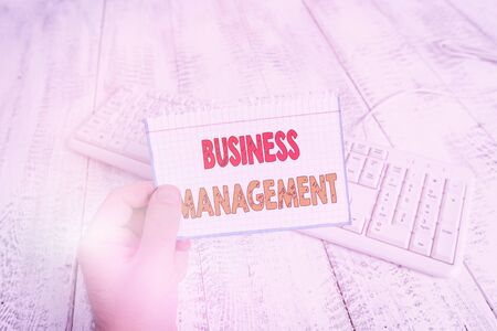 Text sign showing Business Management. Business photo text Overseeing Supervising Coordinating Business Operations man holding colorful reminder square shaped paper white keyboard wood floor