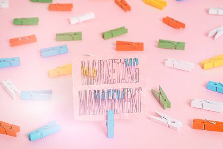 Handwriting text Marketing Management. Conceptual photo Develop Advertise Promote a new Product or Service Colored clothespin papers empty reminder pink floor background office pin
