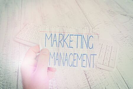 Conceptual hand writing showing Marketing Management. Concept meaning Develop Advertise Promote a new Product or Service Man holding colorful reminder square shaped paper wood floor