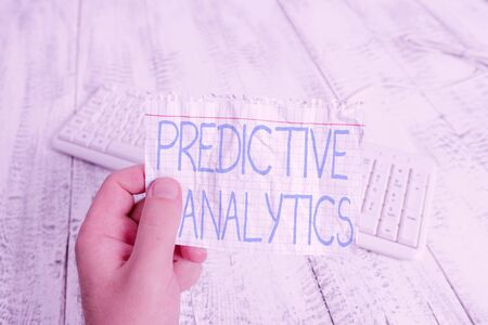 Conceptual hand writing showing Predictive Analytics. Concept meaning Optimize Collection Achieve CRM Identify Customer Man holding colorful reminder square shaped paper wood floor Stock fotó