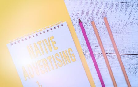 Handwriting text Native Advertising. Conceptual photo Online Paid Ads Match the Form Function of Webpage Blank spiral notepad colored paper sheet markers retro wooden background