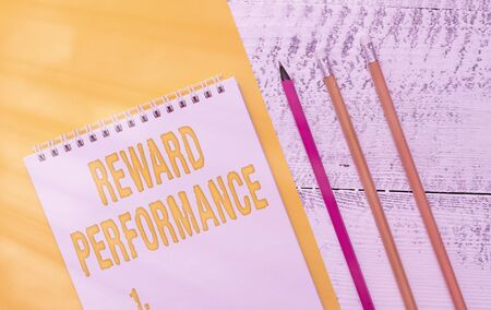 Handwriting text Reward Performance. Conceptual photo Appraisal Recognize workers Relative Worth to the company Blank spiral notepad colored paper sheet markers retro wooden background