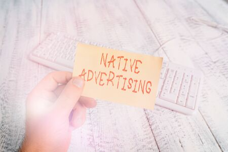 Conceptual hand writing showing Native Advertising. Concept meaning Online Paid Ads Match the Form Function of Webpage Man holding colorful reminder square shaped paper wood floor 写真素材