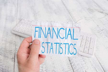 Conceptual hand writing showing Financial Statistics. Concept meaning Comprehensive Set of Stock and Flow Data of a company Man holding colorful reminder square shaped paper wood floor 版權商用圖片