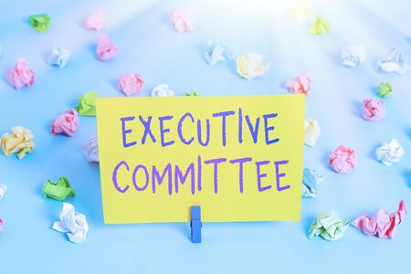 Text sign showing Executive Committee. Business photo text Group of Directors appointed Has Authority in Decisions Colored crumpled papers empty reminder blue floor background clothespin