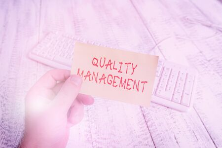 Conceptual hand writing showing Quality Management. Concept meaning Maintain Excellence Level High Standard Product Services Man holding colorful reminder square shaped paper wood floor