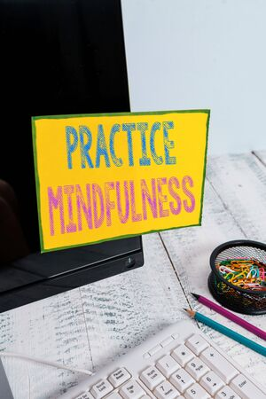 Handwriting text Practice Mindfulness. Conceptual photo achieve a State of Relaxation a form of Meditation Note paper taped to black computer screen near keyboard and stationary 版權商用圖片
