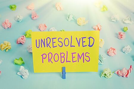 Text sign showing Unresolved Problems. Business photo text those Queries no one can answer Unanswerable Questions Colored crumpled papers empty reminder blue floor background clothespin