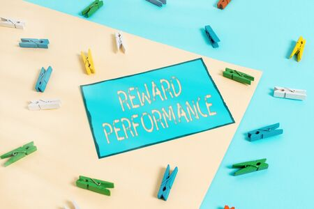 Text sign showing Reward Performance. Business photo showcasing Appraisal Recognize workers Relative Worth to the company Colored clothespin paper empty reminder yellow blue floor background office