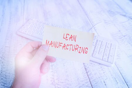 Conceptual hand writing showing Lean Manufacturing. Concept meaning Waste Minimization without sacrificing productivity Man holding colorful reminder square shaped paper wood floor