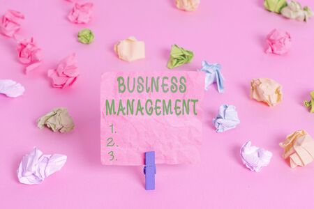 Handwriting text Business Management. Conceptual photo Overseeing Supervising Coordinating Business Operations Colored crumpled papers empty reminder pink floor background clothespin