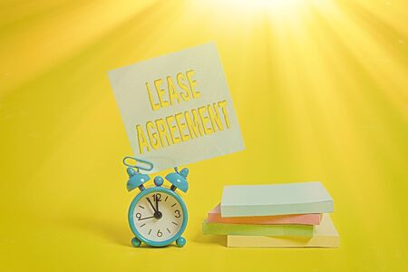 Handwriting text writing Lease Agreement. Conceptual photo Contract on the terms to one party agrees rent property Metal alarm clock blank sticky note stacked notepads colored background