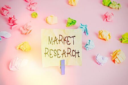 Conceptual hand writing showing Market Research. Concept meaning The acttion of gathering information about consumers Colored crumpled papers empty reminder pink floor clothespin Stock Photo