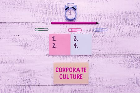 Writing note showing Corporate Culture. Business concept for Beliefs and ideas that a company has Shared values Blank notepads clips marker small alarm clock wooden vintage background