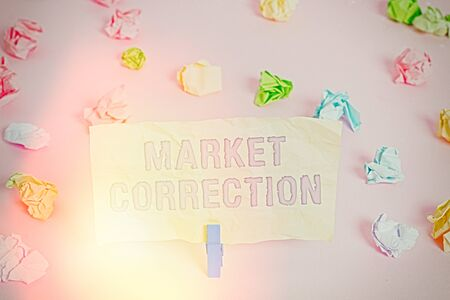 Writing note showing Market Correction. Business concept for When prices fall 10 percent from the 52 week high Colored crumpled papers empty reminder pink floor background clothespin