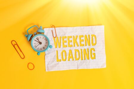 Writing note showing Weekend Loading. Business concept for Starting Friday party relax happy time resting Vacations Metal alarm clock blank crushed note rubber band colored background
