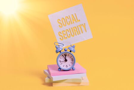 Word writing text Social Security. Business photo showcasing assistance from state showing with inadequate or no income Metal alarm clock blank sticky note stacked notepads colored background