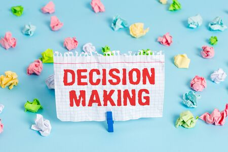 Text sign showing Decision Making. Business photo showcasing The act of deciding between two or more possibilities Colored crumpled papers empty reminder blue floor background clothespin