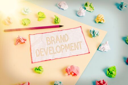 Conceptual hand writing showing Brand Development. Concept meaning Defining the product to excel in the market Promoting Colored crumpled papers empty reminder blue yellow clothespin