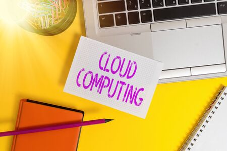 Text sign showing Cloud Computing. Business photo showcasing use a network of remote servers hosted on the Internet Laptop pencil sheet clips container spiral notebook colored background