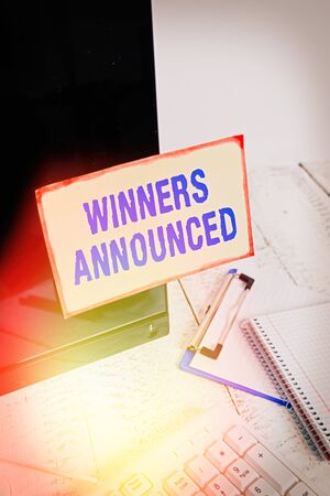 Conceptual hand writing showing Winners Announced. Concept meaning Announcing who won the contest or any competition Note paper taped to black screen near keyboard stationary