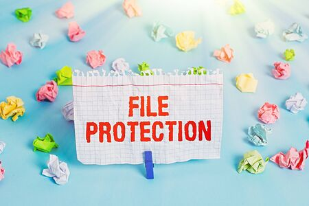 Text sign showing File Protection. Business photo showcasing Preventing accidental erasing of data using storage medium Colored crumpled papers empty reminder blue floor background clothespin