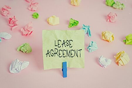 Conceptual hand writing showing Lease Agreement. Concept meaning Contract on the terms to one party agrees rent property Colored crumpled papers empty reminder pink floor clothespin