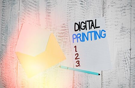 Text sign showing Digital Printing. Business photo showcasing digital based images directly to variety of media Open colored envelope blank sheet letter paper ballpoint wooden background Banco de Imagens