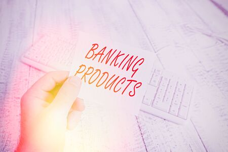 Word writing text Banking Products. Business photo showcasing safe and convenient way or service to accumulate savings man holding colorful reminder square shaped paper white keyboard wood floor Reklamní fotografie